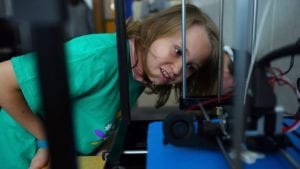 A young Comcast Cares Day volunteers examines some machinery.