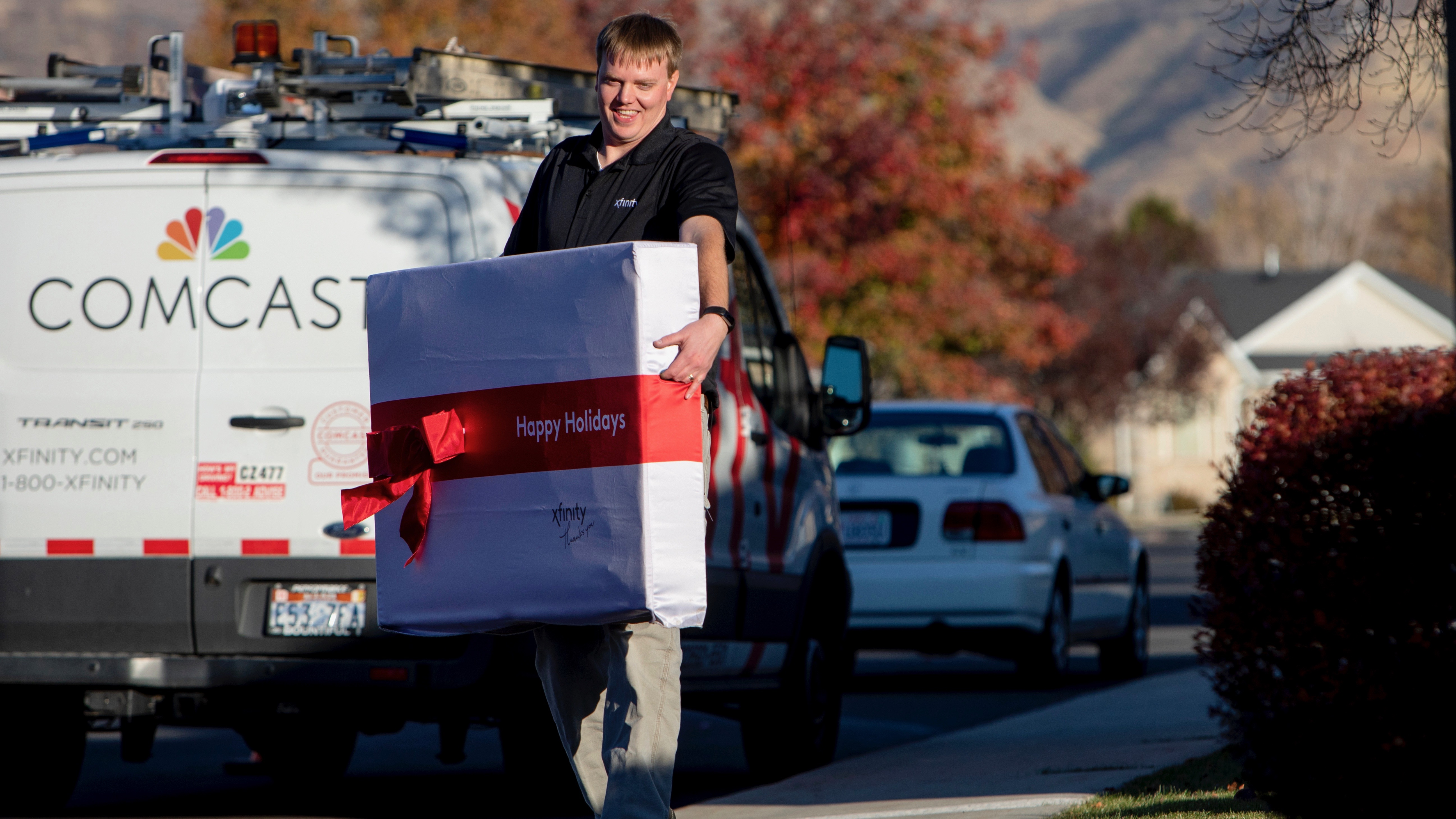 An Xfinity employee carries a large gift box.