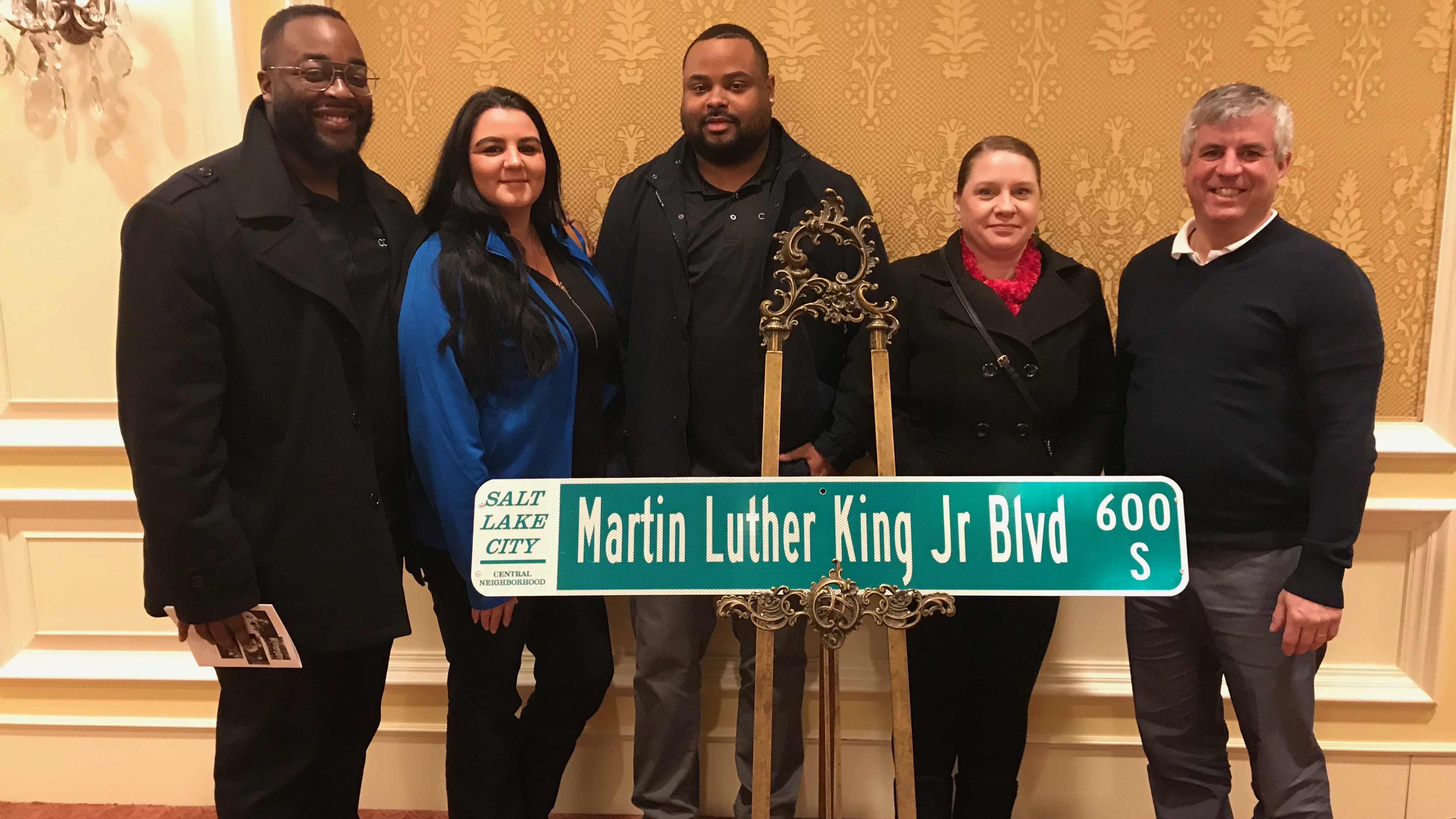 Members of the Comcast Black Employee Network stand in front of a Martin Luther King Jr. street sign.