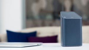 An Xfinity Gateway sits next to a laptop on a desk.