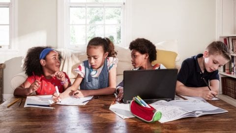 4 kids sitting at a table together working and using a laptop