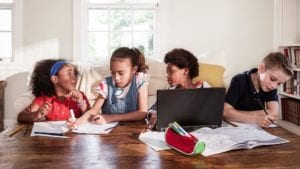 Children do homework together on a table.